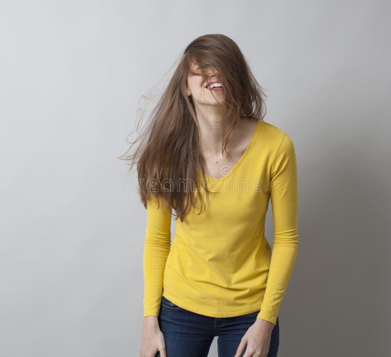 Fille 20s riante nerveusement salissant ses cheveux pour l'amusement photos libres de droits