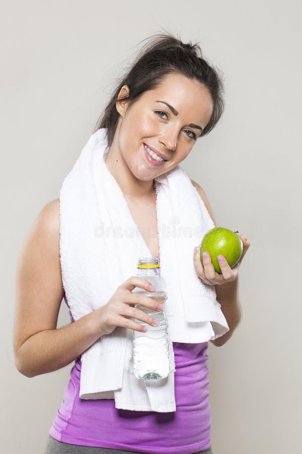 Fille 20s sportive heureuse avec des symboles de santé et de nutrition pour le mode de vie sportif dans des mains image libre de droits