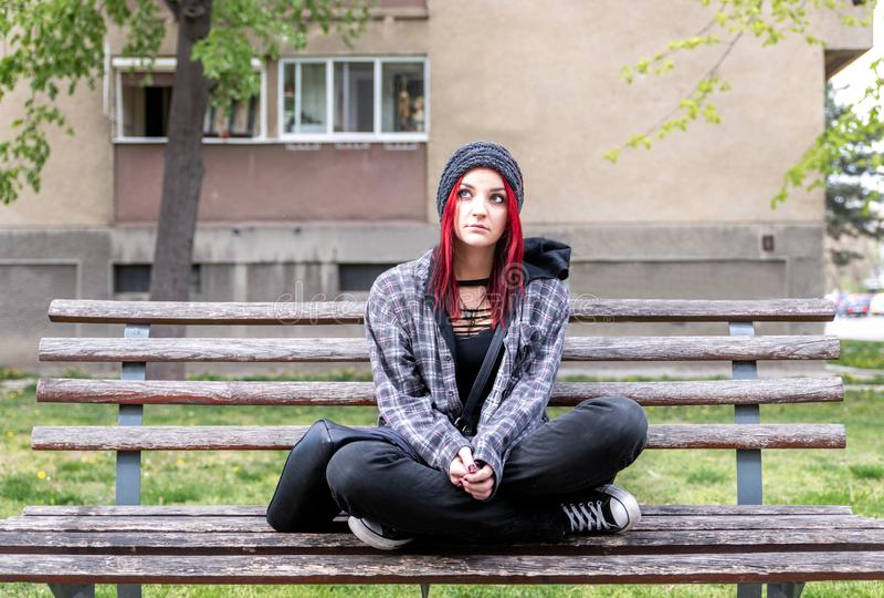 Fille sans abri, jeune fille rouge de cheveux seul s'asseyant dehors avec le chapeau et chemise soucieuse et d?prim?e apr?s qu'el photo stock