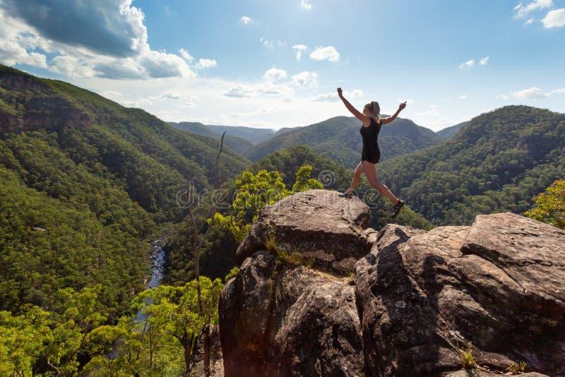 Fille sautant sur la haute falaise rocheuse avec le contexte de rivière de montagne photos libres de droits