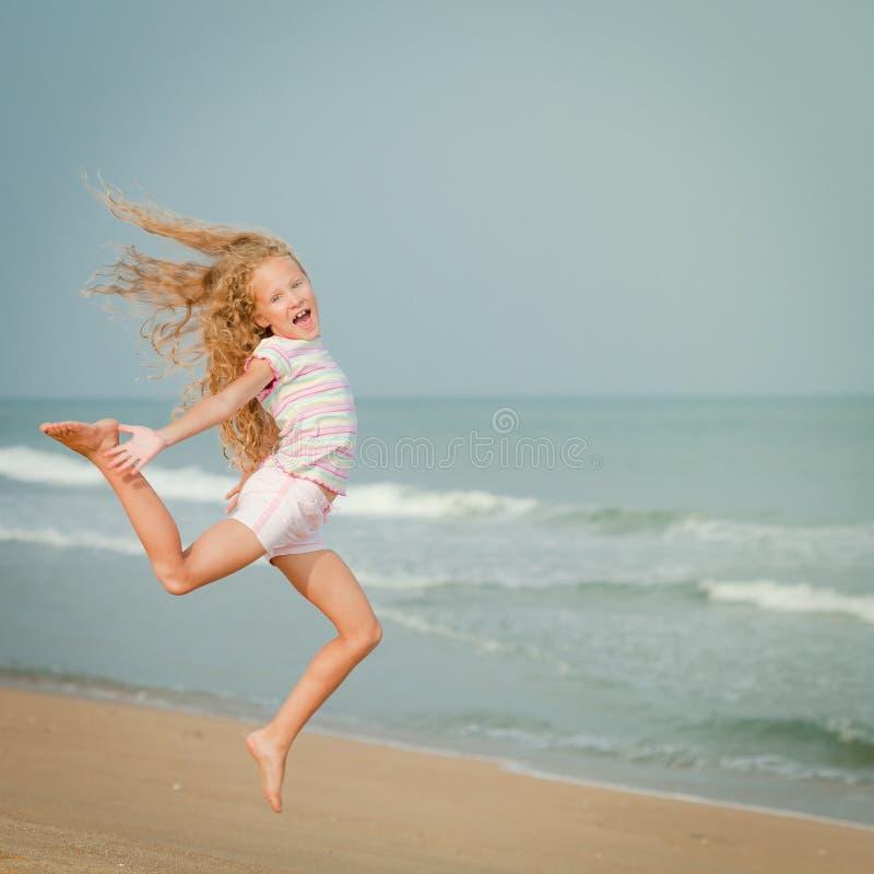 Fille sautante volante de plage au bord de mer bleu images stock