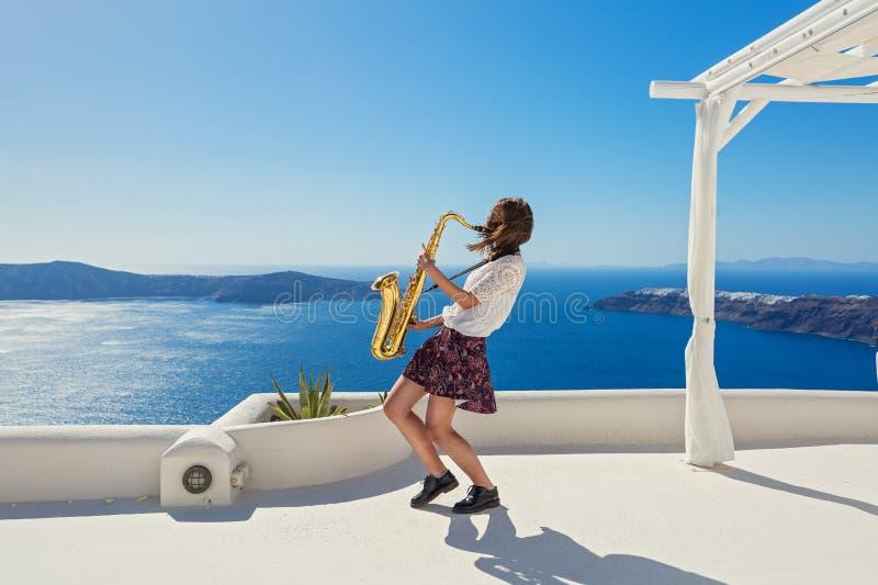 Fille, saxophone et mer images stock