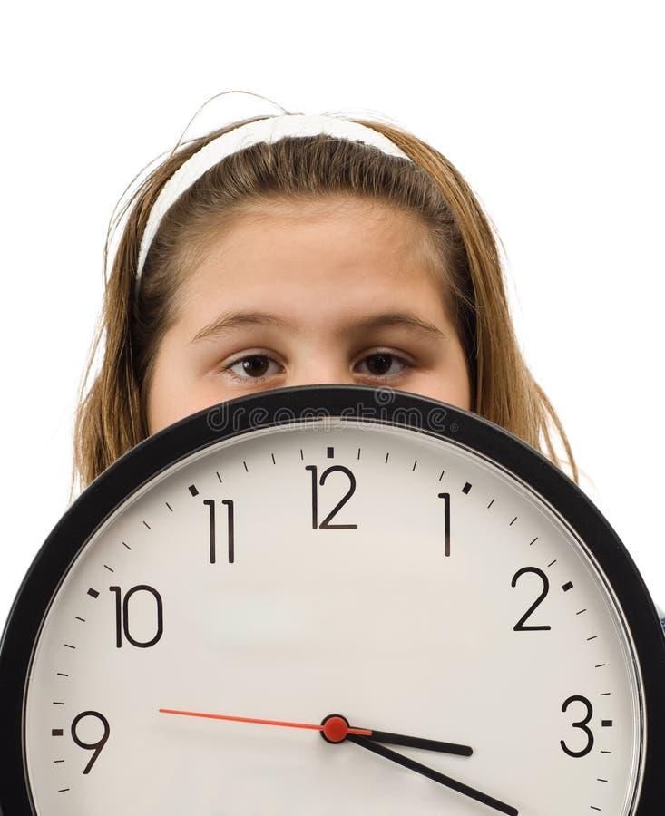 Fille se cachant derrière l'horloge photographie stock