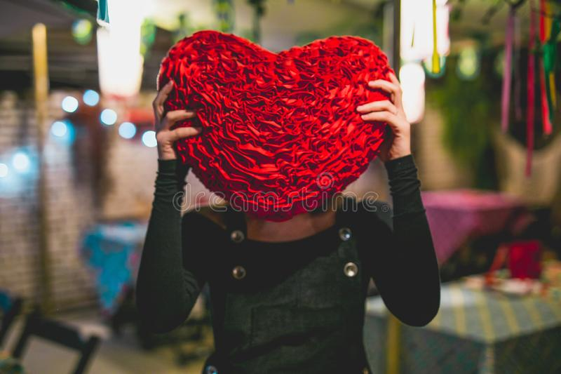 Fille se cachant derrière un oreiller de coeur images libres de droits
