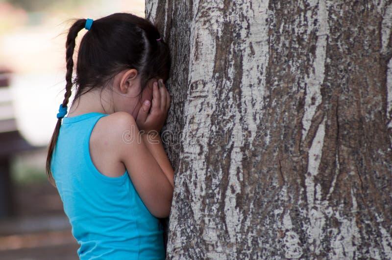 Fille se cachant ou pleurant près d'un arbre photos stock