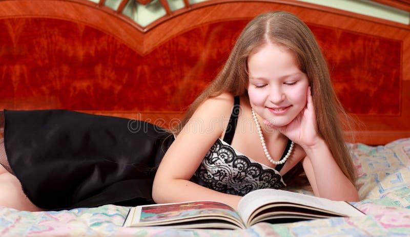 Fille se couchant et livre de relevé photographie stock libre de droits