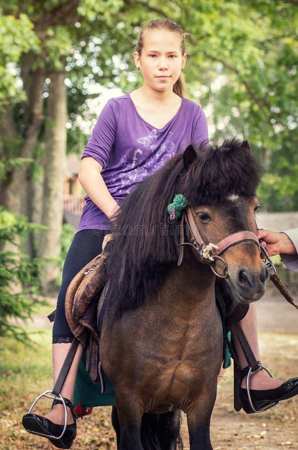 Fille se débarrassant sur un cheval image libre de droits