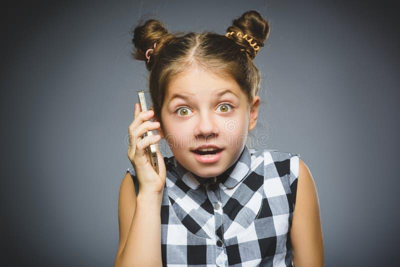 Fille se demandante avec le mobile ou le téléphone portable Enfant de plan rapproché sur le fond gris image stock