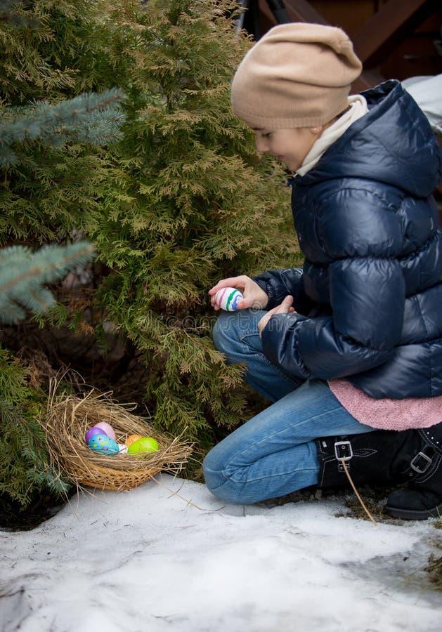Fille se mettant à genoux à côté de l'arbre et sélectionnant l'oeuf de pâques image stock