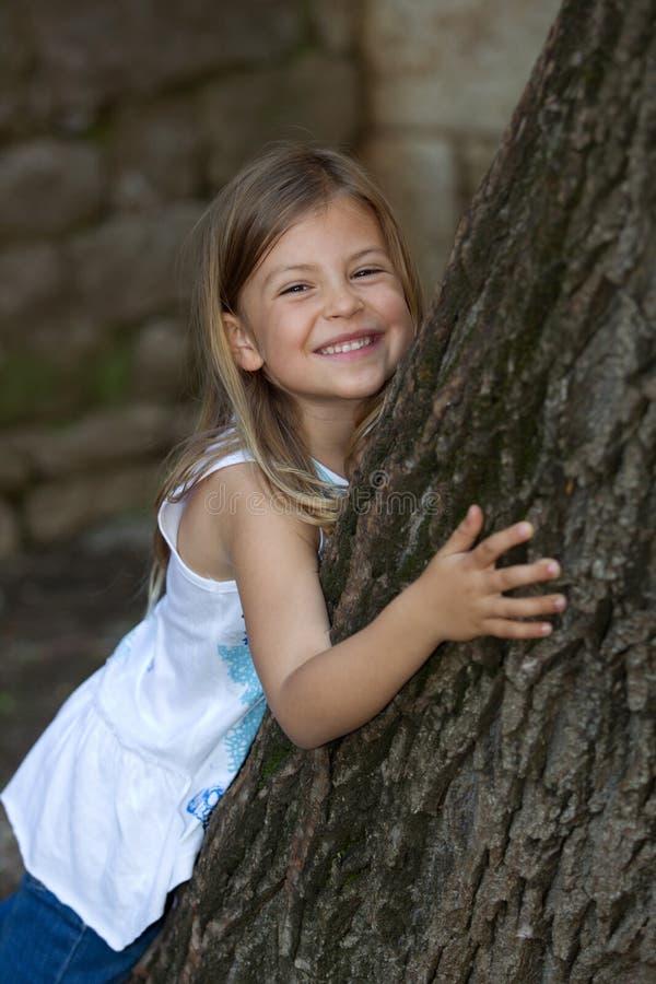 Fille se penchant sur l'arbre de chêne photos libres de droits