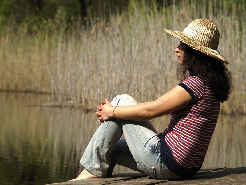 Fille se reposant près du lac photo stock