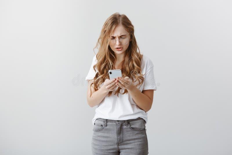 Fille se sentant maladroite envoyant le message au faux numéro Portrait de jeune femme préoccupée attirante en verres, jurant photographie stock libre de droits