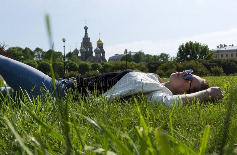 Fille se situant dans une clairière parmi l'herbe verte, sur le backgroun photographie stock libre de droits