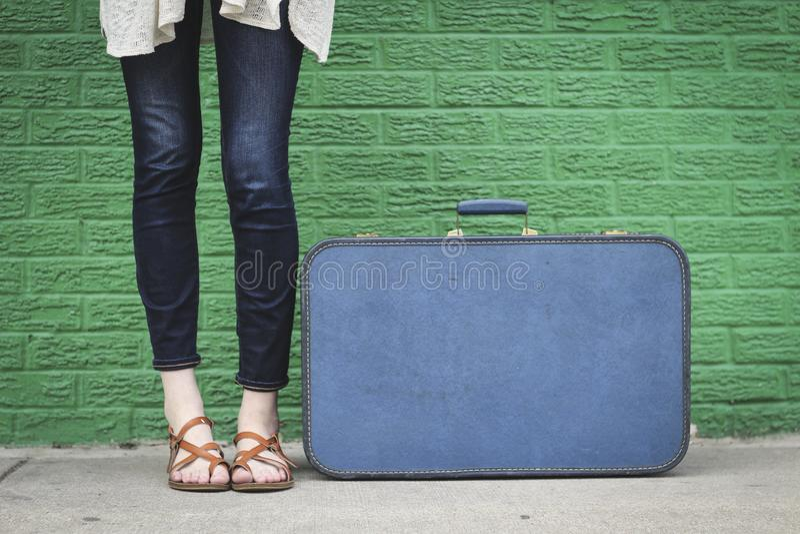 Fille se tenant à côté de la valise photographie stock