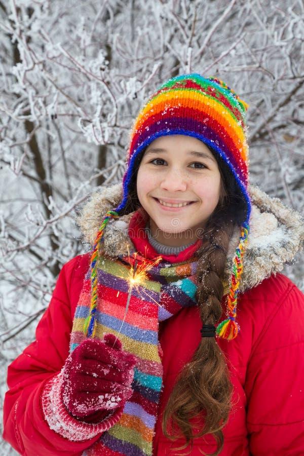Fille se tenant dans des vêtements d'hiver avec des étincelles photos libres de droits