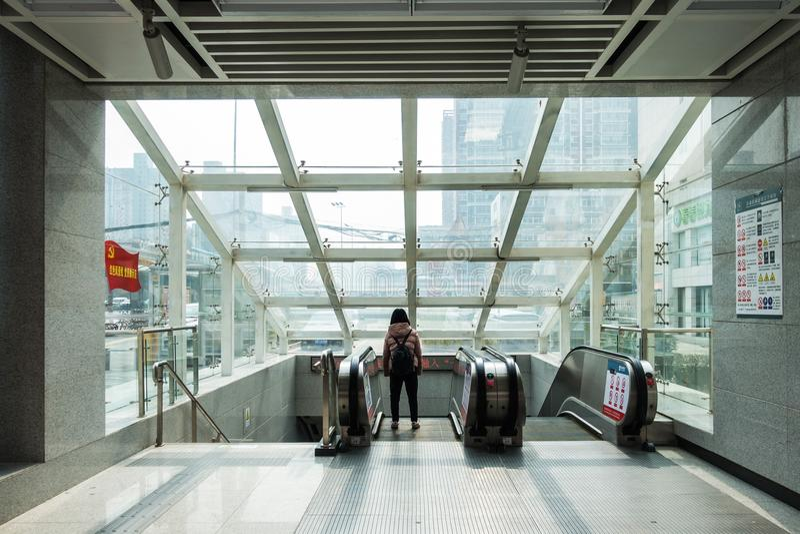 Fille se tenant seul regardante la fenêtre de la station de métro urbaine D image stock