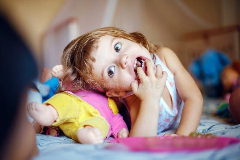 Fille se trouvant avec des doigts dans la bouche image stock
