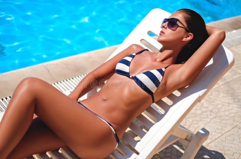 Fille se trouvant et prenant un bain de soleil par la piscine photos stock