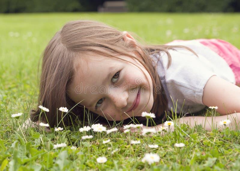 Fille se trouvant sur l'herbe avec la fleur de marguerite photographie stock