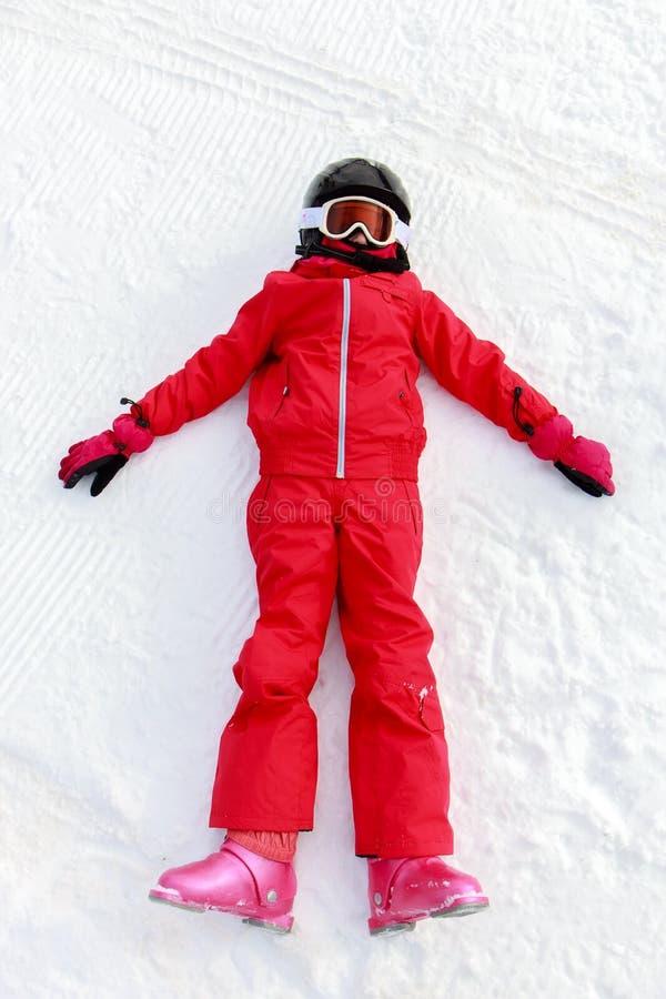 Fille se trouvant sur la neige photos stock