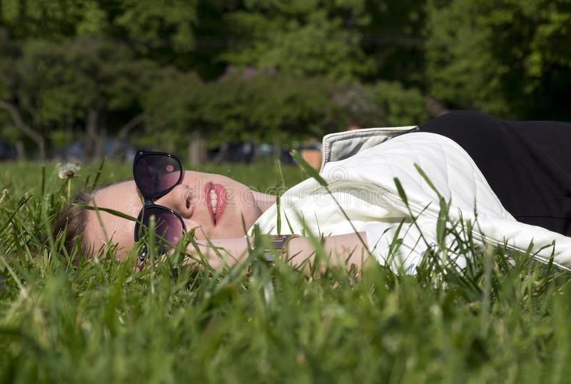 Fille se trouvant sur la pelouse parmi l'herbe photos stock