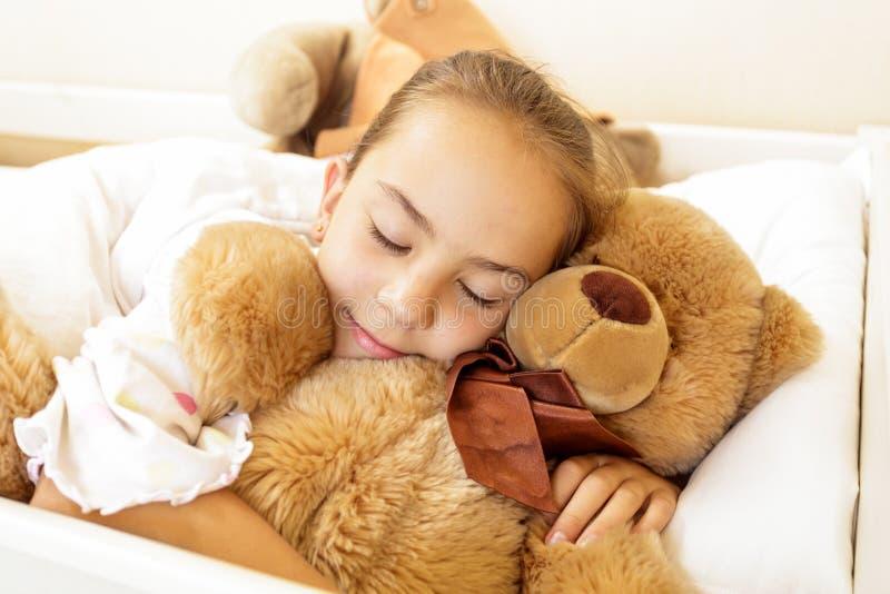 Fille se trouvant sur le lit avec le grand ours de nounours brun images stock
