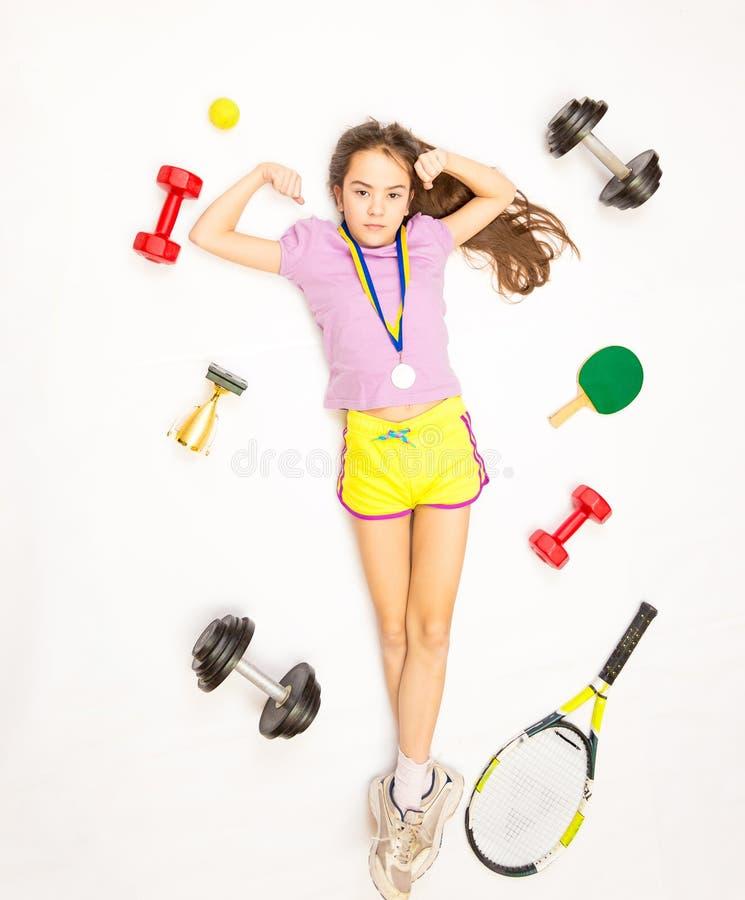 Fille se trouvant sur le plancher avec l'ensemble d'équipement de sport photographie stock