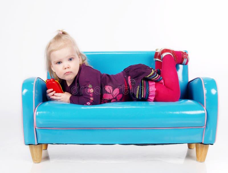Fille se trouvant sur le sofa images stock