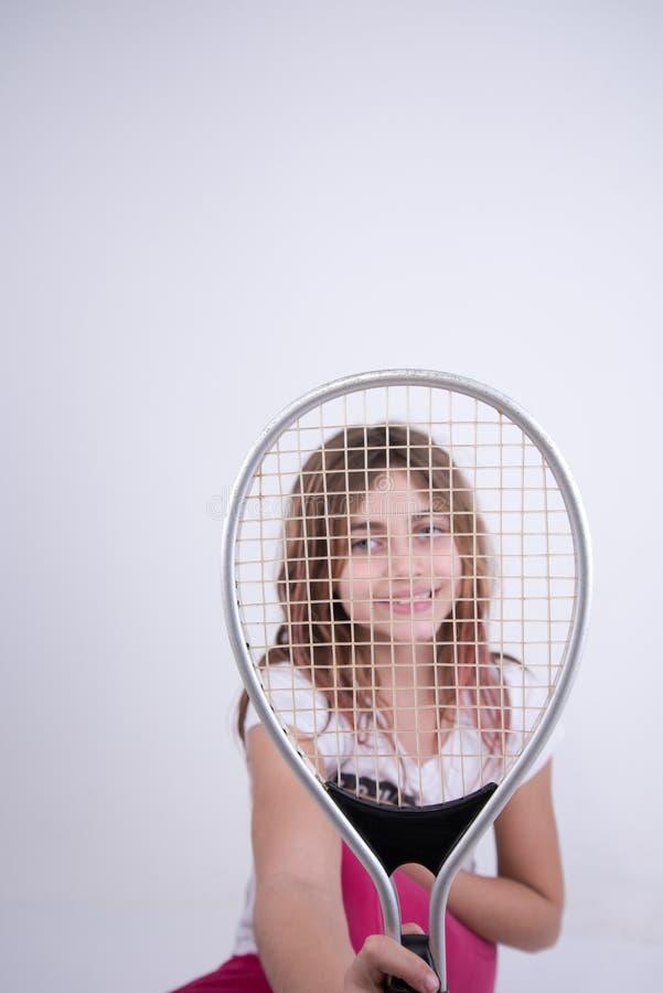 Fille semblant heureuse avec la raquette de tennis photos libres de droits
