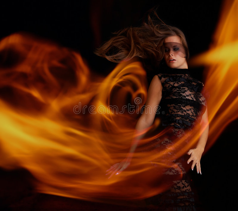 Fille sensuelle dans la danse noire de robe avec la flamme image libre de droits