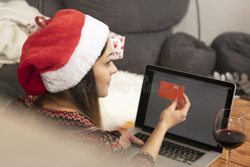 Fille seule dans un chapeau de Noël faisant des emplettes en ligne photos stock
