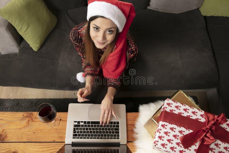 Fille seule dans un chapeau de Noël faisant des emplettes en ligne, vue d'en haut photo stock