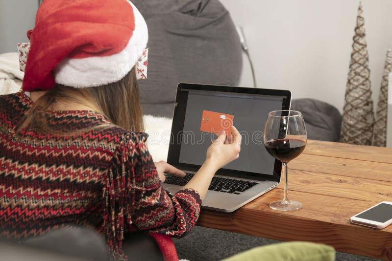 Fille seule dans un chapeau de Noël faisant des emplettes vue en ligne et arrière images libres de droits