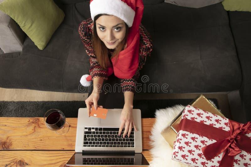 Fille seule dans un chapeau de Noël faisant des emplettes vue en ligne et supérieure photographie stock