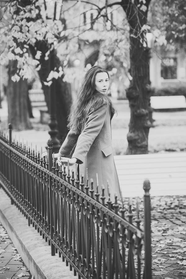Fille seule en parc La jeune femme dans le manteau de chameau marche en parc d'automne photographie stock libre de droits