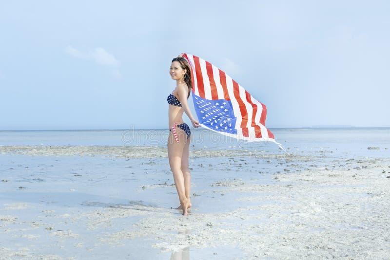 Fille sexy asiatique dans le bikini du drapeau américain tenant un drapeau américain de ondulation sur la plage photographie stock libre de droits