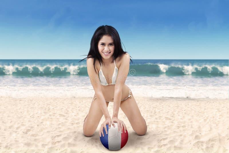 Fille sexy avec du ballon de football à la plage image stock