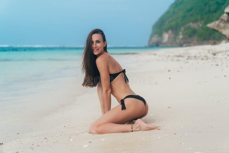 Fille sexy avec le corps sportif dans des poses noires de bikini sur la plage avec l'océan bleu au fond image libre de droits