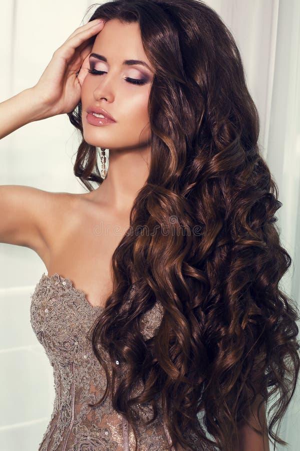 Fille sexy avec les cheveux foncés luxueux dans la robe beige élégante image stock