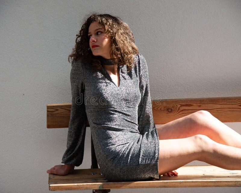 Fille sexy, cheveux onduleux de brune se reposant sur un banc photo libre de droits