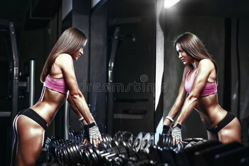 Fille sexy d'athlète de forme physique avec une haltère dans le gymnase photographie stock