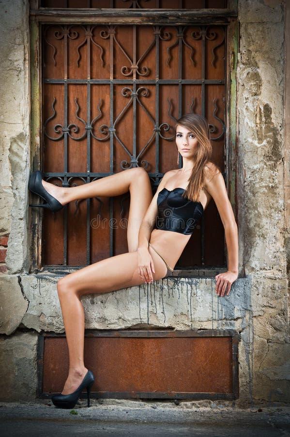Fille sexy dans le bikini posant la mode près du mur de briques rouge sur la rue photos libres de droits
