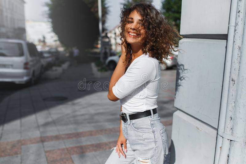 Fille sexy de belle brune marchant dans la ville avec le long vol de cheveux bouclés sur le vent photos libres de droits