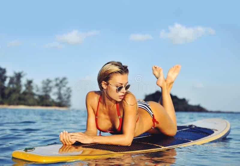 Fille sexy de surfer se trouvant sur une planche de surf en mer photos stock