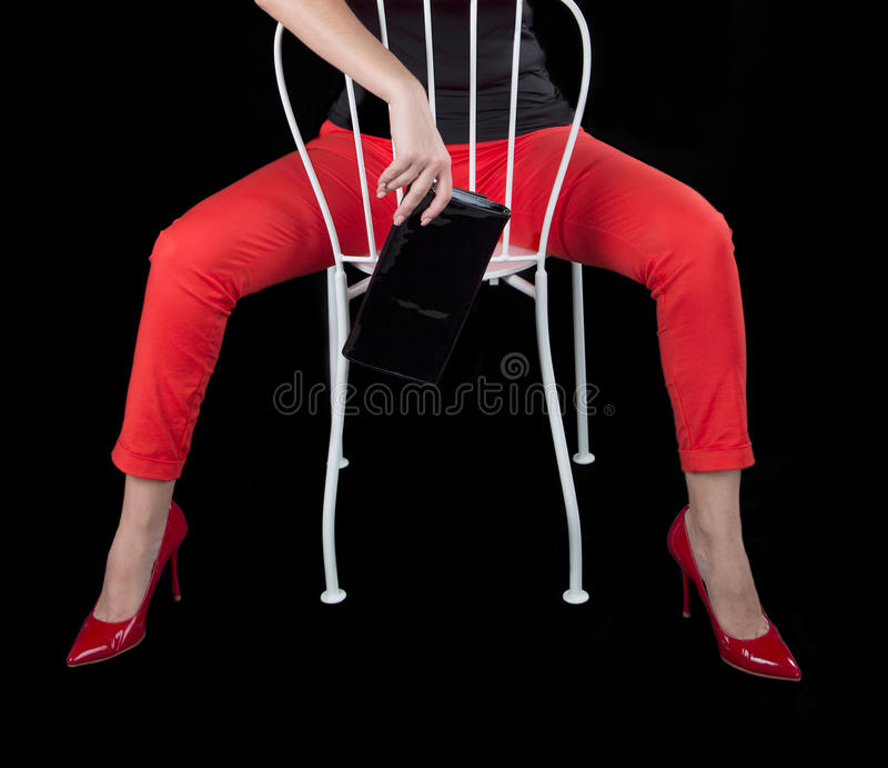 Fille sexy habillée par mode s'asseyant sur la chaise images stock