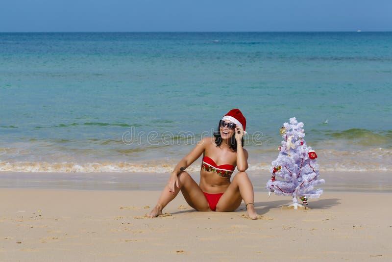 Fille sexy Santa dans le bikini sur un sapin de plage photographie stock