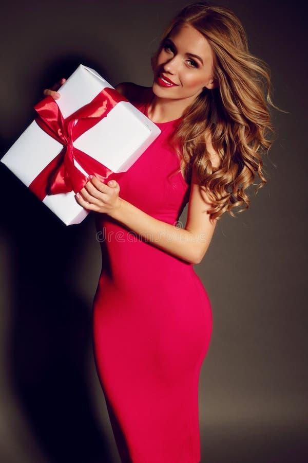 Fille sexy tenant une boîte avec un cadeau et posant dans le studio photographie stock libre de droits