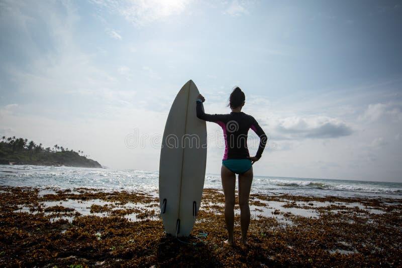 Fille silhouettée de surfer de jeune femme avec la planche de surf blanche photo libre de droits