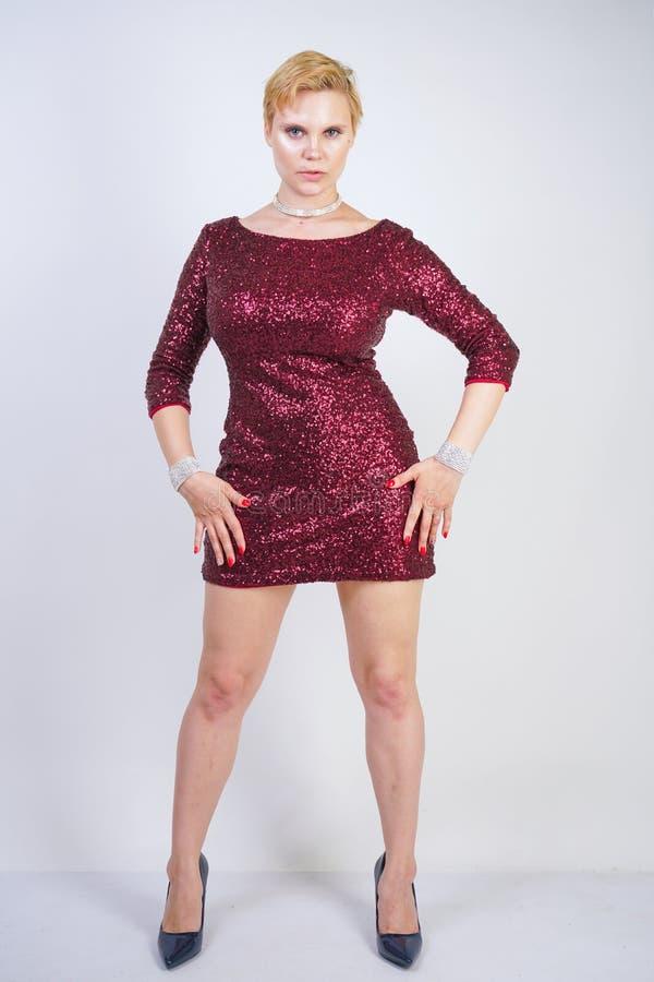 Fille sinueuse caucasienne mignonne avec les cheveux blonds courts et corps plus de taille portant la belle robe élégante de coul images stock