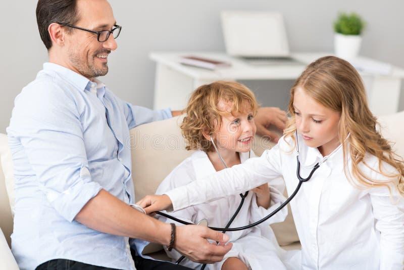 Fille soigneuse examinant avec le stéthoscope photo stock